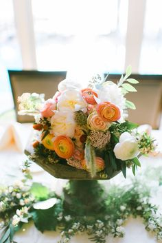 resting on a low vintage birdbath, the bridal bouquet of white peony, peach roses, white ranunculus, rosita vendela roses, white scabiosa, white majolik spray roses, bunny tail grass, pink rice flower, peach ranunculus, scabiosa pods, white spirea, white parrot tulips, elm & seeded eucalyptus is the centerpiece on the head table at the reception.