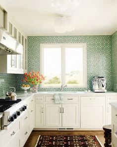 Turquoise tile carried up to the ceiling infuses this space with color and texture, a perfect counterpart to the kitchen's scenic view. Classic ivory-painted cabinetry and a dark area rug...