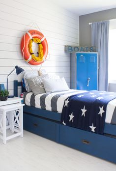 Nautical boy room featuring ship lap, vintage locker, navy and gray paint. Gray stripes and stars bedding complete the nautical feel.