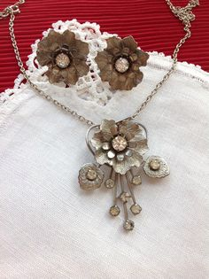 Offered is a delicately fashioned, brushed silver tone floral pendant and screw back earrings. This set is old and very vintage looking. The