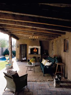 Love this outdoor living area: Exposed Cedar Beams  & posts, bick floor, stucco walls and cozy fireplace!