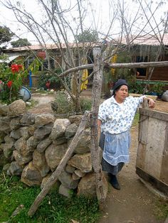 Woman standing at the gate to her house in the Mexican state of Michoacan.