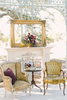 Vintage gold décor for your wedding. Lovely white mantel, empty golf frame with fresh flower arrangement in the center. Beautiful old, vintage chairs with side table in between. Charming and very pretty.