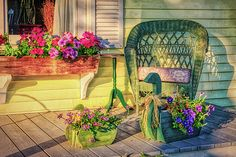Beautiful sunny veranda of a country home in Quebec, Canada, decorated with wooden flower pots, colorful petunias in front of an open window and a comfortable looking high back green wicker chair.