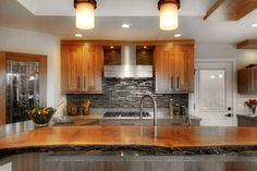 A custom built kitchen from the ground-up. Redesigned light fixtures, cabinets, sink, wooden counter top & flooring.