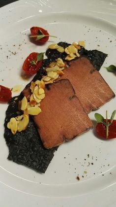 Bottarga di tonno rosso su foglio di pane nero, mandorle tostate e pomodorini confit alla maggiorana.