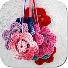 crochet flowers, so cute AND easy to make. these are a few chain made into a ring and joined with a slip stich and then double crochet in the ring, and then loops of chainstiches and finally some more double crochets. Ok I just made that sound more complicated than it is...