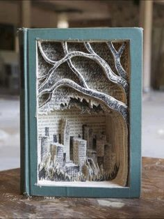 Someone formed a city scape & a tree by cutting out of the pages of a book.
