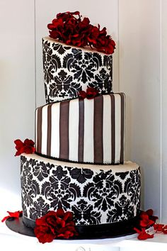 A topsy turvy wedding cake in black and white with stripes, damask and red roses. Sure to impress!