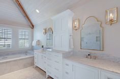 Carrara marble master bathroom - love the plank wood ceiling and the gold accents - part of this full coastal home tour eclecticallyvintage.com