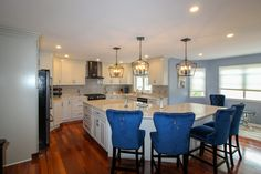 integrating the brown hardwood with grey backsplash and white cabinets. A pop of blue with royal blue velvet bar chairs Updated Kitchen, New Kitchen, Grey Backsplash, Custom Cabinets, Bar Chairs, White Cabinets, Kitchen Flooring, Blue Velvet, Granite Countertops