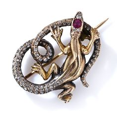 A sinewy, ruby-headed reptile, with an extraordinarily long diamond-studded tail, is artfully sculpted in 18 carat gold in this wonderful and whimsical Victorian-era brooch, circa 1860. 1 3/16 inches by 1 inch.