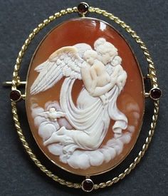 Allegory of the Night (?)      Materials: shell, 18 ct gold and garnets.  Date of the cameo: ca 1910  Origin: Italy  Size of the cameo: 1 13/16 x 1 3/8 inch  With frame: 2 1/8 x 1 3/4  Condition: 100% Mint. No cracks or spots.       Magnificent allegory of the Night hearing two child. On the left there is the owl, symbol of the night. The subject could be also the Aurore: in this case we can suppose she leave away the owl-night.