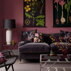 Dark pink walls,aubergine sofas and botanical prints create a vintage feel