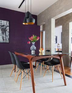 Sala de jantar com estrutura de concreto aparente, parede roxa e mesa com desenho vintage.