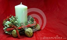 Christmas decorations with candle, pine cone and nut on a red background. Copy space available. For Xmas concept