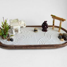 This zen garden sits upon a wooden oval base and features a variety of items  to