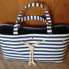 "Blue/white stripe tote-bag with detail Large lined tote or bag with snap center closure and rivet and rope detail on front. Approx. measurements are 17""long, 9"" high, 7"" wide at the bottom. Very nice condition. Great bundle item option. Bags Totes"