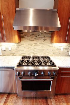 Stainless range with hood in custom, contemporary kitchen on our Suiter Construction built, waterfront home.
