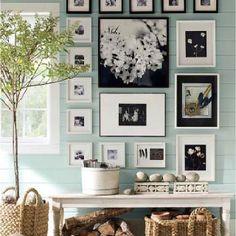 Arrangement of black and white photos above desk