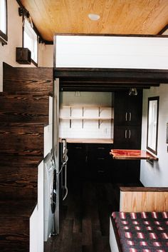 In the kitchen are dark shaker cabinets, a white subway tile backsplash, open shelving, a concrete counter around the sink, and butcher block counters. A cedar live edge table adds rich color to the kitchen.