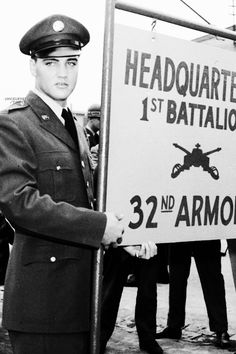 Elvis Presley, the American singer turned soldier, poses beside sign at Friedberg, West Germany, October 2, 1958. Elvis has been assigned to the Third Armored Division.