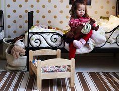 Ein Mädchen zieht ihrer LEKAMMRAT Puppe einen Pyjama an, bevor sie sie in das DUKTIG Puppenbett legt