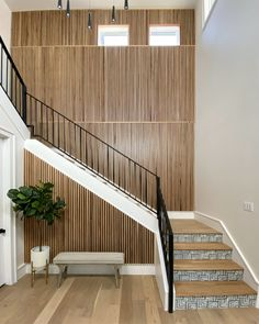Slat Accent Wall Slat Paneling Staircase Paneling Modern paneling The slat wall is made of white oak slats that were attached to a backer board. The backer board was applied to the wall first. The backer board has straight lines routed out and was painted Sherwin Williams Tricorn black. The white oak slats were then nailed into the routed out grooves to ensure that they were all straight. The white oak was sealed with a clear coat and left to be its natural color Modern Paneling Design Ideas… Slat Wall, Staircase, Open Dining Room, Office Paint Colors, Accent Wall Panels, Home, Custom Homes, New Construction, Real Estate