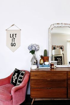 This Young Entrepreneur's LA Home Is Filled With Affordable Finds | pink velvet chair, let it go art, and midcentury dresser