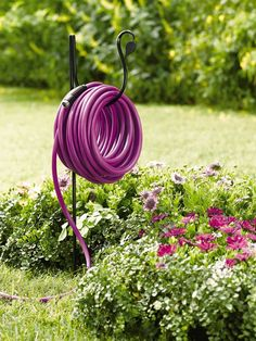 hose holder with coiled up purple hose in a garden full of flowers Garden Hose Storage, Garden Hose Holder, Water Hose Holder, Spring Garden, Lawn And Garden, Water Garden, Garden Beds, Garden Supplies, Garden Tools
