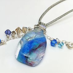 Elixir de Mar: é um colar de estilo esportivo-fino, criado através de um trabalho artesanal de vidros tipo murano, fio de prata e cristais Swarovski facetados em cordão de couro natural.