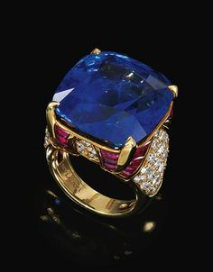 SAPPHIRE, RUBY AND DIAMOND RING, BULGARI. Centring on a cushion-shaped sapphire to a mount enhanced with buff-top rubies and brilliant-cut diamonds, size 54, signed Bulgari.