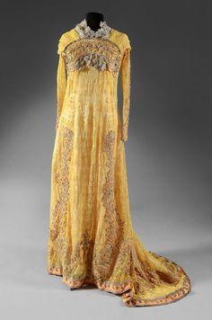 Tea gown, vers 1910. Tulle brodé de fleurettes jaune citron, fond de robe en satin crème. Corsage taille haute à manches longues ajustées, empiècement plissé souligné d'un arc de fleurs stylisées en soutache argent et application de satin. Jupe évasée à traîne longue brodée de palmes et festons,