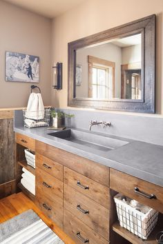 In the owners' bathroom, the reclaimed oak used else- where in the house is stained for a darker, more refined look. The countertop is concrete, and the mirror surround is zinc. The photo features the wife's grandfather, an avid skier, … Continue reading →