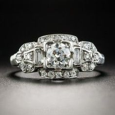 This consummate Art Deco dazzler, die-struck and hand-finished in platinum, circa 1920s-30s, features a bright and beautiful European-cut diamond weighing .46 carat. The scintillating stone, accompanied by a GIA Diamond Grading Report stating: J color - VS1 clarity, centers a classic buckle motif mounting embellished all around with small single-cut diamonds and a pair of vertically-set straight baguette diamonds. Embossed chevrons adorn the top of the currently size 6 1/2 ring shank. A…