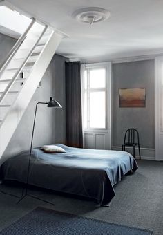Modern bedroom in dark gray shades with a few orange details. The chair is from By Lassen, the lamp is from Serge Mouille and the textiles are from Wood Notes.