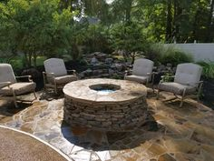 A new fire pit & stone patio sit beside this beautiful Pondless Waterfall in this backyard retreat. Stone Masonry, Backyard Retreat, Outdoor Kitchens, Fireplaces, Pond, Waterfall, Nursery, Patio, Outdoor Decor