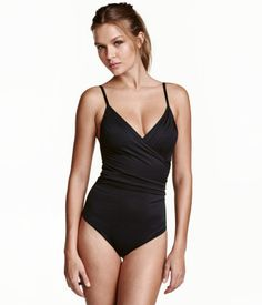 Black. Fully lined shaping swimsuit with sculpting effect on stomach, back and seat. Wrapover top section with lightly padded cups and boning. Decorative