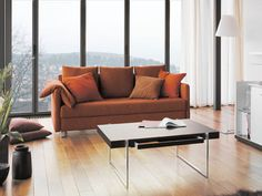 Example of brown sofa with orange pillows