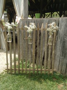 Tobacco stick picket fence with vintage milk bottles will really add charm to your rustic barn wedding venue that's pleasing to your guest! Nailing the pickets together and some nails rusting for a few months makes this an eye catcher for a wedding! I used jute tied around the neck of the bottle with a long loop to hang from.