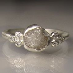 Natural, uncut, rough, conflict free white diamond set in fine silver bezel on sterling silver band. 1.3mm brilliant cut diamonds set into classic