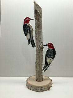 Stained glass woodpeckers on a piece of birch.
