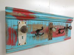 Hello and thank you for stopping by. Here is a re-purposed coat rack. Its made using real antique door knobs, door knob back plates and antique triple acorn hooks. Put them all together and Its a completely functional coat rack. What a statement in your entry way. No matter where it hangs, it will make a statement. The wood has been painted turquoise and barn red, then distressed to match the age of the knobs.  This coat rack measures about 30 inches long and about 11 1/2 inches tall. I ...