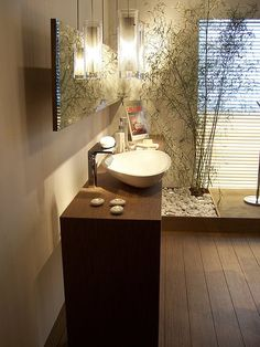 A Contemporary Zen bathroom with Wood Flooring and Eye-Catching Lighting Fixtures