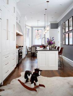 Серая кухня в интерьере: 75+ избранных классических и современных дизайнерских решений http://happymodern.ru/seraya-kuxnya-v-interere-foto/ Однотонные серые стены, деревянный пол, белый кухонный гарнитур, подвесные лампы со стеклянным абажуром – общее нейтральное оформление современной кухни. Акценты: сиреневый диван, геометрическая обивка обеденных стульев, высокие коричневые анатомические стулья, иллюстрации на стенах и букет живых цветов