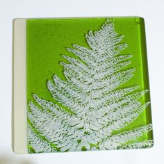 "This trivet is transparent fern green glass with an opaque ivory 1/2"" stripe, and features a fern screen printed in ivory enamel, then fused to about 1400 degrees in a kiln. It is screen printed, kiln"