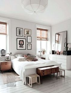 Neutral bedroom with gallery pictures wood and painted floorboards