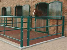 Small turnout pens with rubber floor and accessible gaps (for people, not horses)