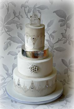 Silver and white wedding cake, with edible lace and silver leaf.