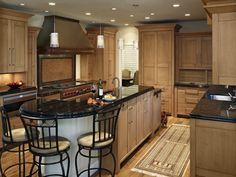 Transitional styling in a two toned color scheme of light maple and dark granite creates a balance in this kitchen.  The dimensional door brings more form to the design.